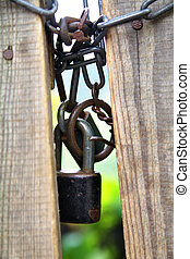 Closed gate - Closed wooden gate with old padlock with chain