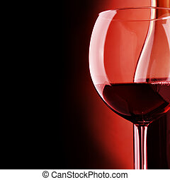 Red wine - Glass and bottle of wine over black background