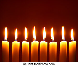 Eight alight candles close-up over red background
