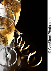 Champagne - Couple glasses of champagne with gold streamer...
