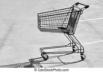 Empty shopping cart - Single empty shopping cart on asphalt