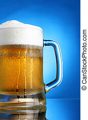 Mug of beer close-up with froth over blue background