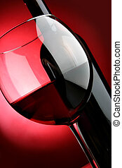 Big glass and bottle of red wine over red background