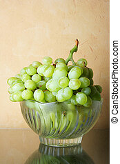 Still-life with bunch of grapes and glass bowl