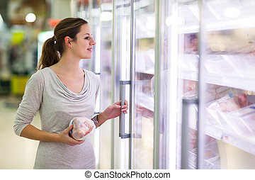 Young woman shopping for meat in a grocery store (color...