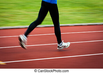 Young woman running at a track and field stadium motion...