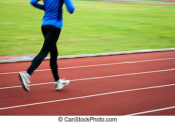 Young woman running at a track and field stadium (motion...