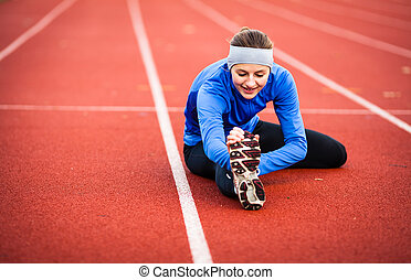 Young woman stretching before her run - Young woman...