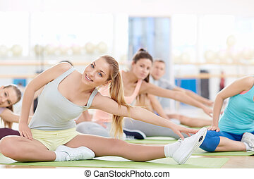 Stretching - Women doing stretching in fitness club