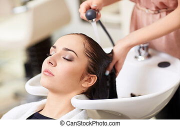 In the barbershop - Barber washes the girls head in the...