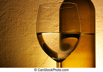 Glass and bottle of white wine over textured background