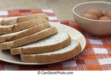 Sliced of wheat bread with eggs in a bowl.