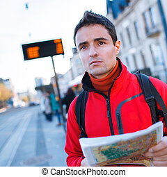 Just arrived: handsome young man studying a map