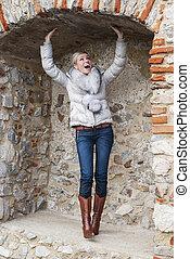 Beautiful blond woman posing in brick niche - A portrait of...