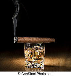 Whiskey and cigar on wooden background close up