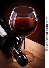 Red wine bottle and glass on a wooden table.