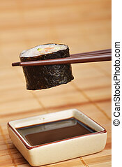 fresh sushi - sushi between chopsticks ready to dip into...