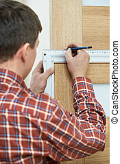 carpenter at door installation - Male handyman carpenter at...