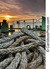 Winch with rope on  boat in the sea at sunset