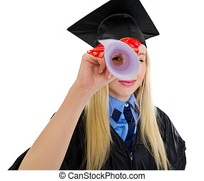 Young woman in graduation gown looking through diploma