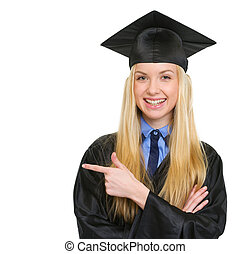 Smiling young woman in graduation gown pointing on copy...
