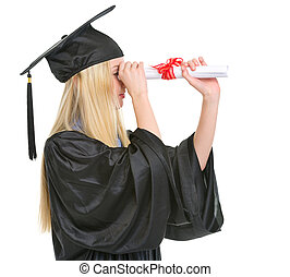 Young woman in graduation gown looking into distance through...