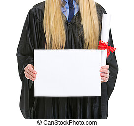 Closeup on woman in graduation gown with diploma showing...