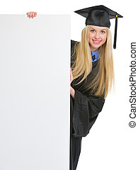 Smiling young woman in graduation gown looking out from...