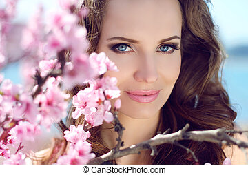 Outdoors portrait of beautiful smiling woman model in pink...