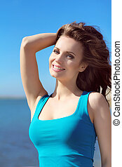 Portrait of attractive young woman feeling free against blue...