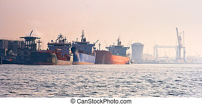 Harbour with tankers on a colorful misty sunrise in...