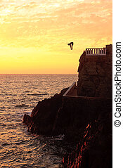 Cliff diver off the coast of Mazatlan at sunset