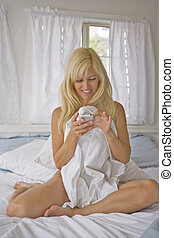 Nude Woman smiling while checking her Text Messages - Nude...