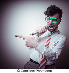 funny stylish businessman singing on gray background