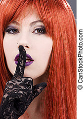 hush - portrait of beautiful redhead with finger on lips