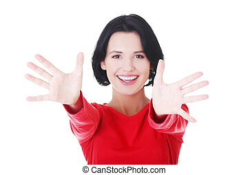 Woman pointing with both hands towards the camera - Portrait...