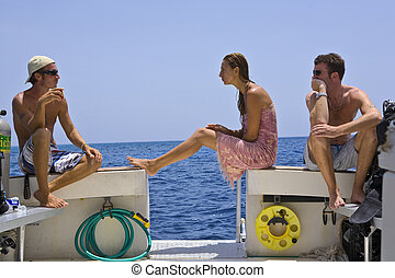 Surface interval between Dives - Three Divers relax on a...