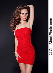 Beautiful sexy woman in red dress with curly hair posing over dark background
