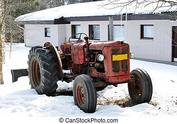 old red tractor on a farm in winter