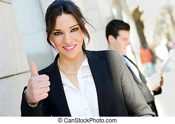 Attractive businesswoman showing thumb up sign - Portrait of...