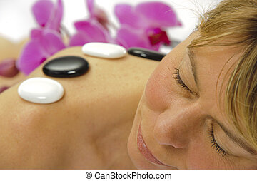 spa massage - woman getting spa with massage stones
