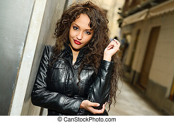Attractive black woman in urban background wearing leather...