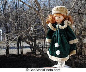 Victorian Porcelain Doll against a wooded background.