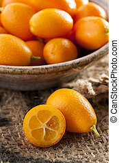 Fresh Organic Raw Kumquats Citrus Fruit against a background