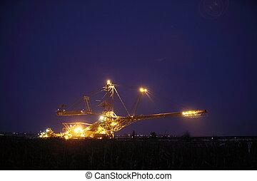 giant excavator in a coal open pit evening - bucket wheel...