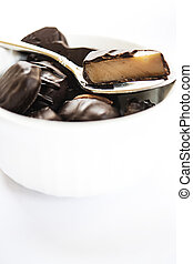 Dark Chocolate Treats in White Bowl With Spoon - A delicious...