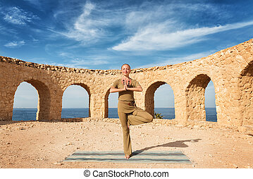 Beautiful woman practicing yoga outdoors against blue sky