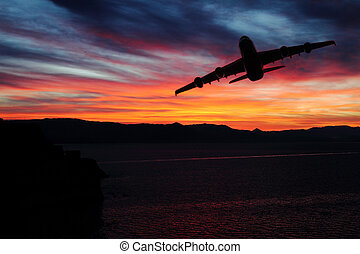 Scenic view of sunrise over the mountains with airplane over the sea