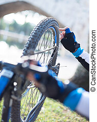 Close-up Of A Man's Hand Repairing Bicycle Wheel; Outdoors