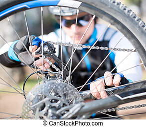 Young Man Repairing Bicycle Wheel; Outdoors